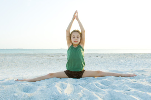 Girl doing yoga on beach